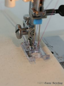 Sew with a straight stitch with twin needles as you would a standard needle